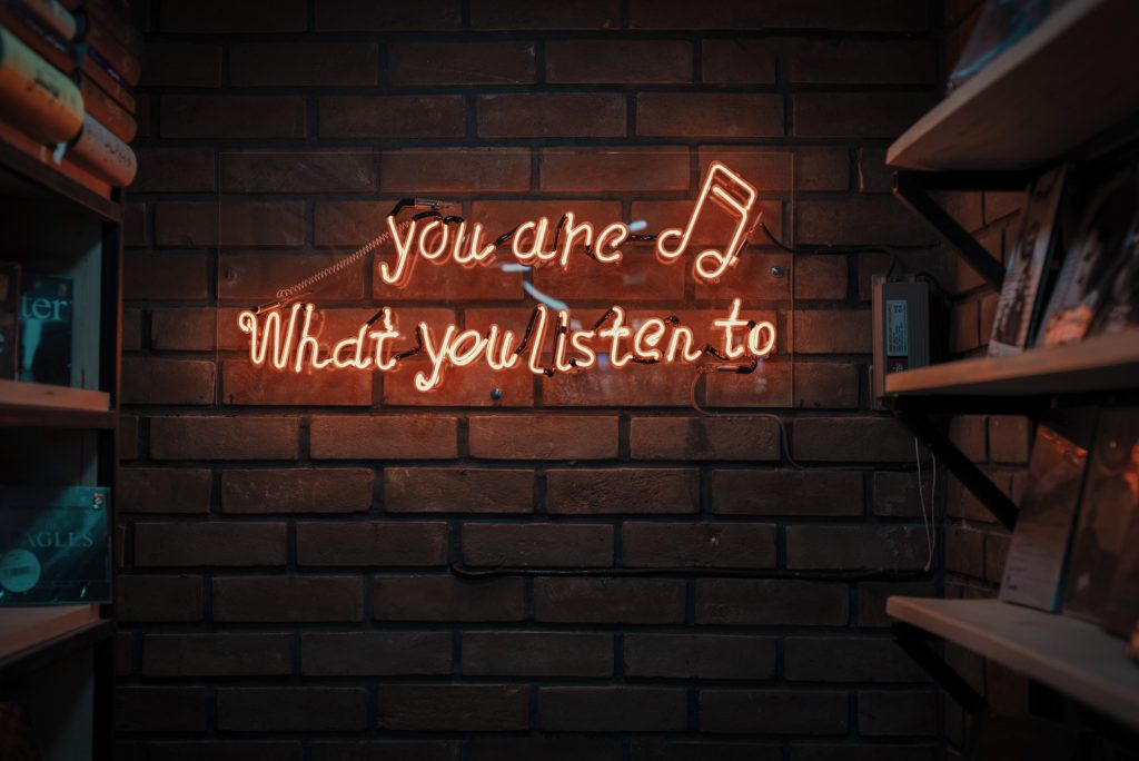 "Neon sign on brick wall. ""You are what you listen to"" Photo by Mohammad Metri on Unsplash"